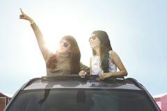 Молодые женщины смотря что-то на крыше с окошком автомобиля Стоковое Фото