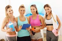 Молодые женщины собирают обсуждать план здоровья на спортзал стоковая фотография rf