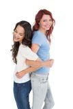 Молодые женщины стоя спина к спине с блокировать руками Стоковые Изображения