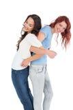 Молодые женщины стоя спина к спине с блокировать руками Стоковая Фотография RF
