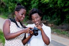 Молодые женщины счастливые, наблюдая изображения на экране их камеры Стоковые Изображения RF