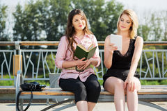 Молодые женщины с книгой и цифровым compute таблетки Стоковые Изображения
