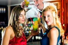 Молодые женщины с коктеилями в клубе или баре Стоковое Фото