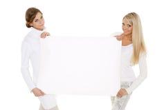 Молодые женщины с пустой доской для текста Стоковое Фото