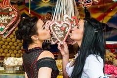Молодые женщины с сердцами пряника на Oktoberfest Стоковые Изображения