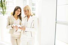 Молодые женщины с таблеткой в офисе Стоковые Изображения