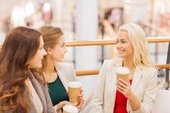 Молодые женщины с хозяйственными сумками и кофе в моле Стоковое Изображение RF