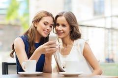 Молодые женщины с smartphone и кофе на кафе Стоковые Изображения