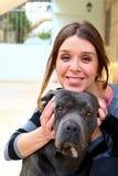 Молодые женщины усмехаясь с черной собакой Стоковое Фото