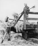 Молодые женщины bucking сено (все показанные люди более длинные живущие и никакое имущество не существует Гарантии поставщика что Стоковая Фотография