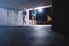 Молодые женщины jogging под мостом на ноче Стоковое Изображение RF