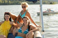 Молодые женщины sunbathing на шлюпке Стоковое Изображение RF