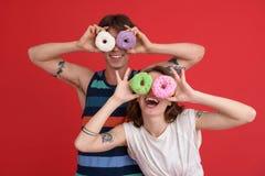 Молодые жизнерадостные 2 друз стоя с donuts Стоковые Изображения RF