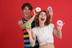 Молодые жизнерадостные 2 друз стоя с donuts Стоковая Фотография RF