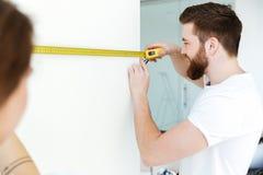 Молодые жизнерадостные любящие пары в новой квартире делают ремонт Стоковые Изображения RF