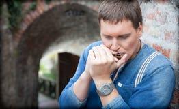 Молодые игры игрока губной гармоники на улице Стоковые Изображения RF