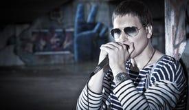 Молодые игры игрока губной гармоники на улице Стоковая Фотография