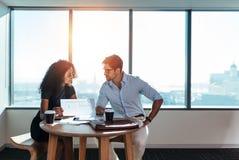 Молодые инвесторы дела обсуждая деловые вопросы в офисе Стоковое Изображение RF