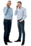 Молодые исполнительные власти говоря через мобильный телефон стоковые изображения rf