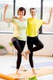 Молодые и более старые женщины делая йогу Стоковые Изображения