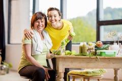 Молодые и более старые женщины с здоровой едой внутри помещения Стоковая Фотография