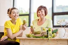 Молодые и более старые женщины с здоровой едой внутри помещения Стоковое Изображение RF