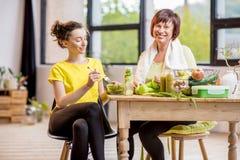Молодые и более старые женщины с здоровой едой внутри помещения Стоковая Фотография RF