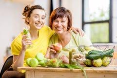 Молодые и более старые женщины с здоровой едой внутри помещения Стоковые Фото