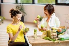Молодые и более старые женщины с здоровой едой внутри помещения Стоковое Изображение