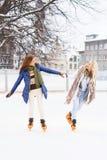Молодые и милые девушки катаясь на коньках на внешнем катке Стоковые Изображения RF