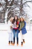 Молодые и милые девушки катаясь на коньках на внешнем катке Стоковые Фото