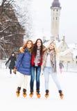 Молодые и милые девушки катаясь на коньках на внешнем катке Стоковое фото RF