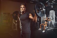 Молодые и подходящие пары в спортзале делая разминку Стоковое Изображение
