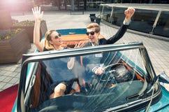 Молодые и привлекательные пары сидя в роскошном ретро автомобиле Стоковые Фотографии RF
