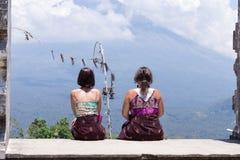 Молодые кавказские женщины туристские около балийского индусского виска Вулкан Agung на предпосылке Редкий взгляд тюкованный Стоковые Фотографии RF