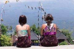 Молодые кавказские женщины туристские около балийского индусского виска Вулкан Agung на предпосылке Редкий взгляд тюкованный Стоковое Изображение