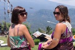 Молодые кавказские женщины туристские около балийского индусского виска Вулкан Agung на предпосылке Редкий взгляд тюкованный Стоковые Фото