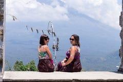 Молодые кавказские женщины туристские около балийского индусского виска Вулкан Agung на предпосылке Редкий взгляд тюкованный Стоковое Фото