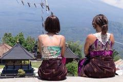 Молодые кавказские женщины туристские около балийского индусского виска Вулкан Agung на предпосылке Редкий взгляд тюкованный Стоковая Фотография