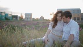 Молодые кавказские пары сидят в поле сток-видео