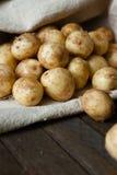 Молодые картошки (младенца) в мешке на деревянной таблице Стоковое фото RF
