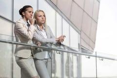 Молодые коммерсантки на перилах офиса смотря прочь Стоковое фото RF