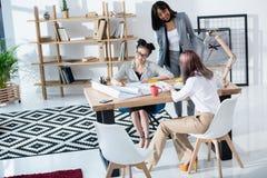 Молодые коммерсантки работая вместе с светокопиями в современном офисе Стоковое Фото
