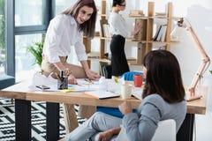 Молодые коммерсантки работая совместно в современном офисе и обсуждая Стоковое Фото