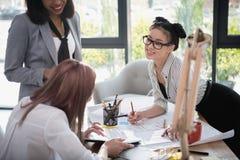 Молодые коммерсантки работая совместно и обсуждая новый проект в офисе Стоковые Изображения RF