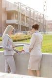 Молодые коммерсантки работая совместно на компьтер-книжке пока стоящ против офисного здания Стоковое фото RF