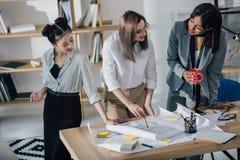 Молодые коммерсантки работая с светокопиями и обсуждая проект в офисе Стоковые Фото
