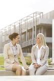 Молодые коммерсантки смотря один другого пока сидящ против офисного здания Стоковое Изображение