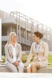 Молодые коммерсантки смотря один другого пока сидящ против офисного здания Стоковые Изображения RF