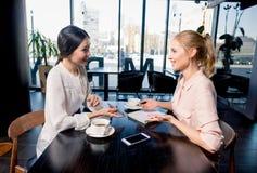 Молодые коммерсантки смотря тетрадь и обсуждая проект на перерыве на чашку кофе Стоковое Изображение RF